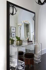 clear console table in front of black leaning mirror
