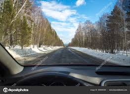 View of the road through the windshield. Snow on the sidelines. Wet asphalt  road. Blue sky