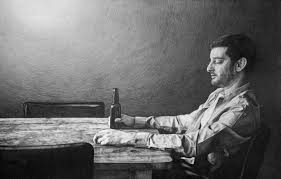 black and white ilration of figure holding bottle while seated alone at a table