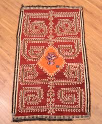 hand knotted persian gabbeh tribal rug with orange medallion and spidery pattern on a red