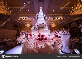 wedding cake and flowers decorations with chandelier on ceiling stock photo