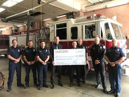 lincoln skinner president of the south pasadena prayer breakfast presents a check for 1 000 to the local fire department the donation will go to those
