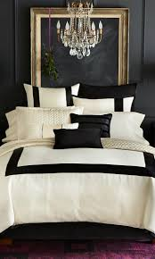 luxury black and white bedroom with crystal chandelier and linen sheet also brass mirror