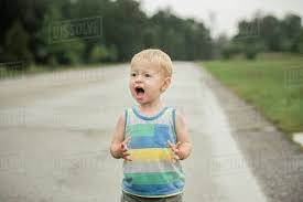 cute boy shouting while looking away during rainfall on road