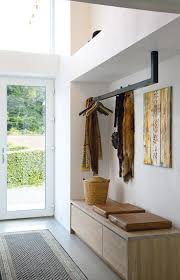Spacious entryway with a beautiful wooden bench storage you can sit on and  a hanging rail