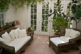 fresh and comfortable sunroom design with casual furniture of rattan sofa  with white bolster and cushions