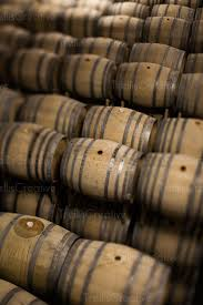 stacked oak barrels maturing red wine. Winery Cellar Filled With Stacked Oak Wine Barrels. Barrels Maturing Red