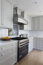 grey kitchen features grey cabinets painted benjamin moore brushed aluminum paired with light gray countertops and subway tiled backsplash over light oak