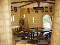 a narrow passage way leads into the camelot room that has a circular table for the knights painted stone interior colorful hanging banners and a tall