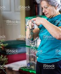 Untangle Christmas Tree Lights Senior Adult Woman Adjusting And Untangling A String Of