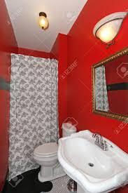Piccolo bagno rosso con lavandino bianco e doccia con pavimento