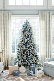 A beautifully flocked Christmas tree is decorated with icy blue ornaments  and ribbons. A few other shades are also incorporated in this dcor like  silver, ...