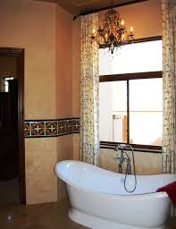 lovely bathroom with curved bathtub and chandelier