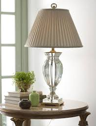 lovely room setting with solid crystal lamp books and small glass vases decorating