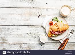 white table top view. Fresh Croissant Sandwich With Ham, Cheese And Salad Leaf Coffee On White Table, Top View Table