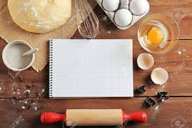Notebook And Raw Dough With Ingredients On Kitchen Table Cooking