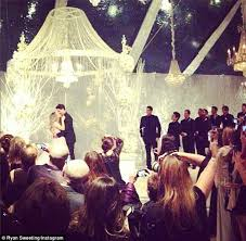 just married the couple kissed under a canopy as they are surrounded by friends and