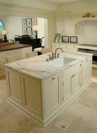 white coastal style kitchen with two islands off white cabinets travertine tile floors
