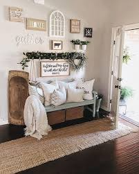 a welcoming entryway with a jute rug a blue bench printed pillows a