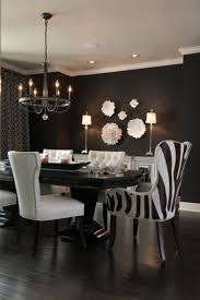 light aristocrat chandelier glossy black dining table black walls white mirrored buffet white nailhead trim side chairs zebra captain dining chairs