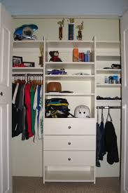 children clothing storage unit is simple and easy to reach utilizing wall niches added shelves drawers and hanging rods and covered with double doors