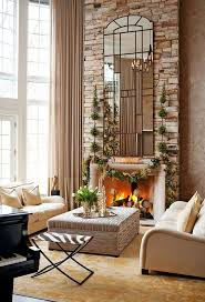 love the stone brick wall what a beautiful fireplace with tall mirror and artificial topiary trees on each side along with the faux garland