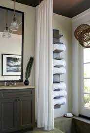 bathroom with white curtain and wall towel storage