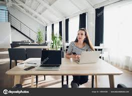 woman office furniture. Adult Woman At A Modern Office Desk, Working On Laptop And Phone, Looking Away, Thinking About Post, Full-time Blogger, Seeking For Inspiration \u2014 Photo By Furniture N