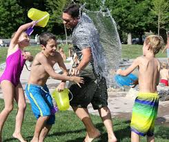 children having a water fight with their au pair in new zealand