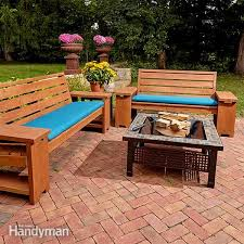 this patio bench offers comfortable seating with built in end tables to set your drinks at parties and barbecues