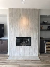 luxury vinyl plank floors surround this beautifully refaced fireplace with large format porcelain tiles with wave like texture