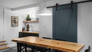 blue sliding barn door conceals doorway next to rustic live edge dining table