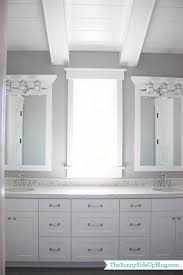 over white framed mirrors accented with triple sconces on gray wall over white double vanity topped with caesarstone organic white quartz countertops