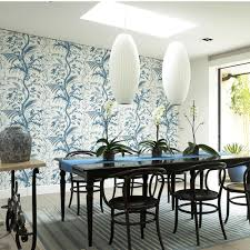 Dining room with pendant lights, black dining table and patterned feature  wallpaper