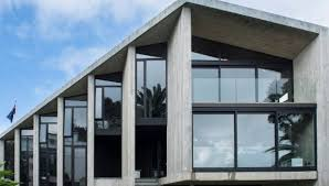 concrete home designs. six fin walls march down the side of large concrete house that features in home designs