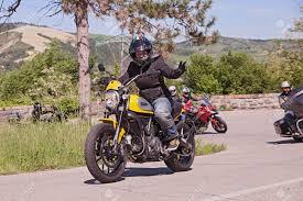 biker riding italian motorbike ducati scrambler with a group