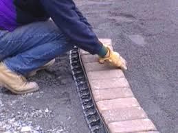 laying bricks along driveway edge