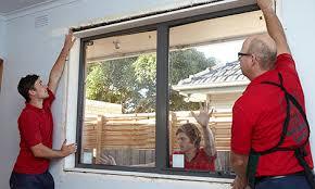 men lifting aluminium window into place