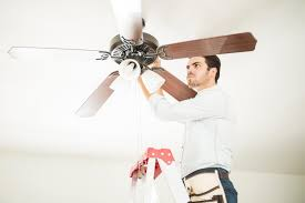 homeowner tightening the s on a noisy ceiling fan
