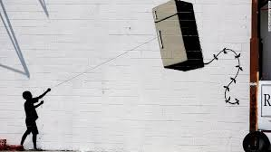 a silhouette of a child holding a refrigerator shaped kite is seen on a wall on most famous wall artist with graffiti artist banksy says he offered 60 paintings in central park