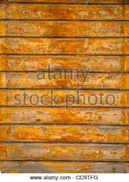 Texture wooden fence with horizontal yellow boards and faded paint