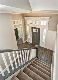 entryway with gray stair rail and white balers crystal entry chandelier tuftex carpet with manningtons restoration collection laminate flooring in