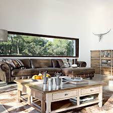 Rustic living room with brown leather couch and distressed wood coffee  table and bookshelf.