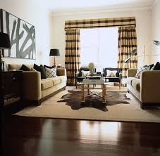beige and black living room with black and white abstract art over face to face beige 3 cushion sofas accented with black pillows flanked by glossy black black beige living room