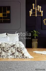 black poster above bed in grey bedroom interior with gold chandelier and plant real photo
