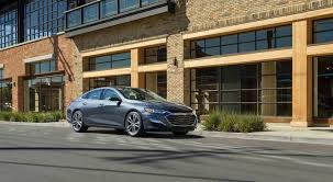 a gray 2019 chevy malibu in front of a tab brick building