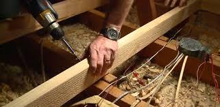Screwing frame to attic floor joists.