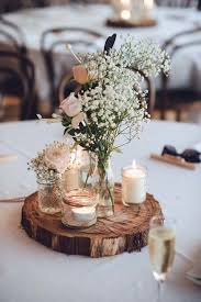 log round centerpiece with jar candles and vase of baby breath and roses