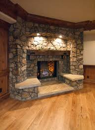 indoor stone fireplace. decorations : interesting stones exposed indoor fireplace with lighting and side seats on wooden floor shelf mantel plus wood beam stone