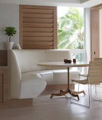 furniture white upholstered curved bench with round table and rattan wicker chair placed on wooden floor as well as dining stools and benches plus wood